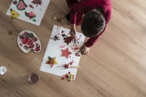 Aerial view of a kid kneeling down on a wooden floor doing Christmas painting decorations .