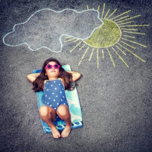 Cute little baby girl having fun outdoors, drawing on asphalt sun and tanning under it, happy childhood in summer camp, active summertime holidays