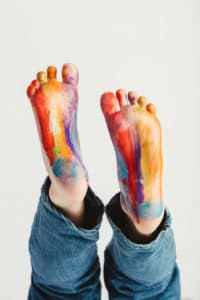 Kid's feet painted in rainbow colors. Messy fun. Creative activity.