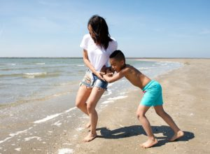 Portrait of a young mother and son playing at the beach