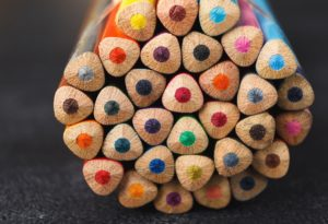 Stack of colorful pencils tips on dark table, art background. Set for drawing back texture, copy space